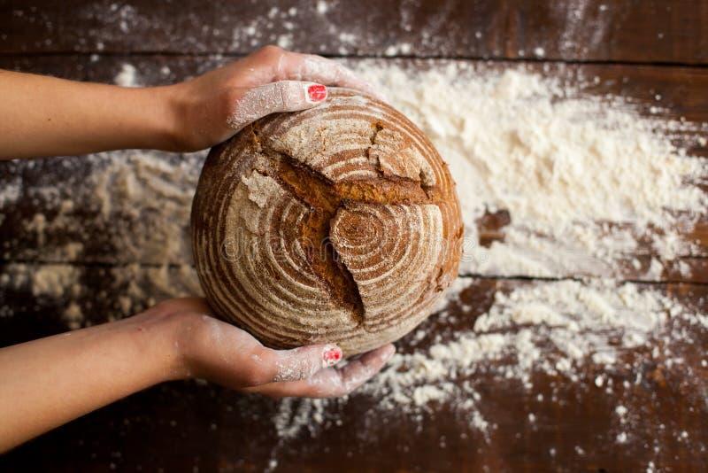 Καφετί ψωμί στα χέρια στοκ εικόνες