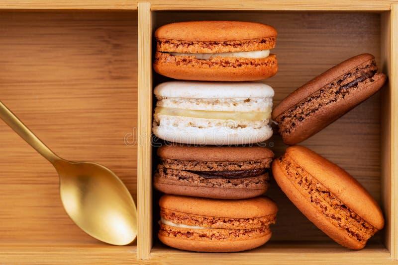 Καφετιά και άσπρα γαλλικά macarons ή macaroons, που συσσωρεύονται σε ένα κιβώτιο μπαμπού με το χρυσό κουτάλι στοκ εικόνες