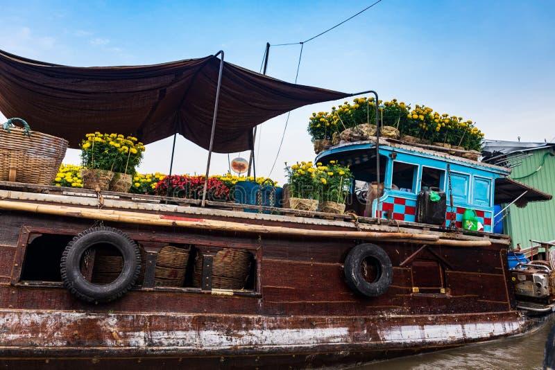 Καφετιά και μπλε βάρκα ή sampan φέρνοντας κίτρινα και κόκκινα λουλούδια για το νέο εορτασμό έτους Tet, Mekong δέλτα, Βιετνάμ στοκ εικόνα με δικαίωμα ελεύθερης χρήσης