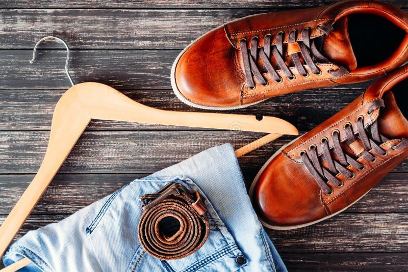 Καφετιά παπούτσια, τζιν και ζώνη δέρματος περιστασιακά στη σκοτεινή ξύλινη τοπ άποψη υποβάθρου στοκ φωτογραφίες