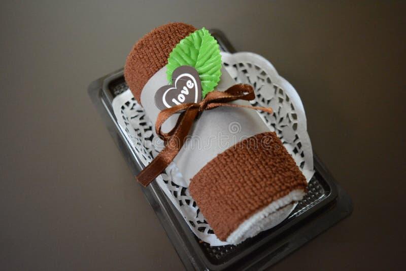 Καφετιά πετσέτα προσώπου που κυλιέται σε έναν σωλήνα με την καρδιά και την αγάπη στοκ εικόνες
