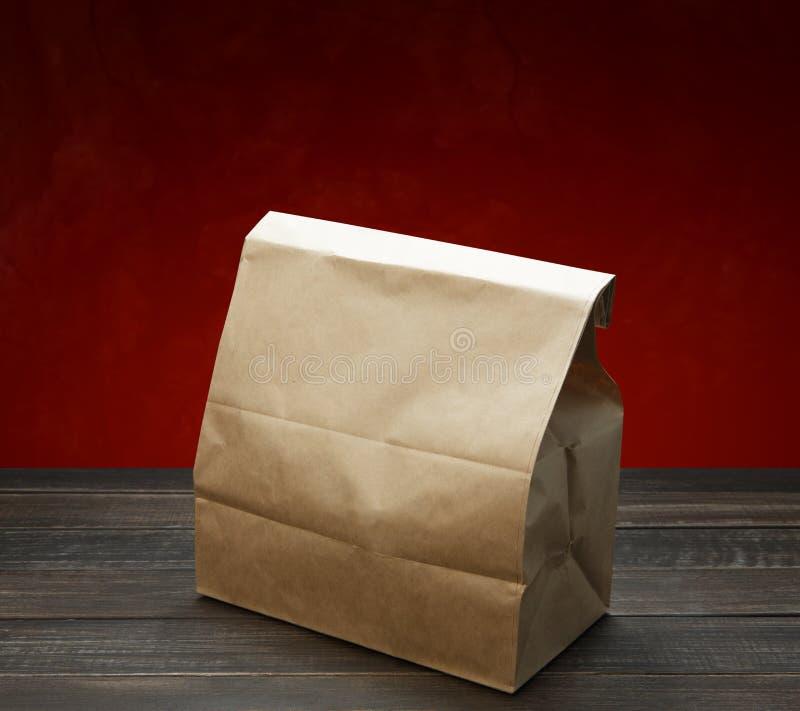 Καφετιά τσάντα εγγράφου του Κραφτ για το μεσημεριανό γεύμα ή τρόφιμα στον ξύλινο πίνακα στοκ φωτογραφία με δικαίωμα ελεύθερης χρήσης