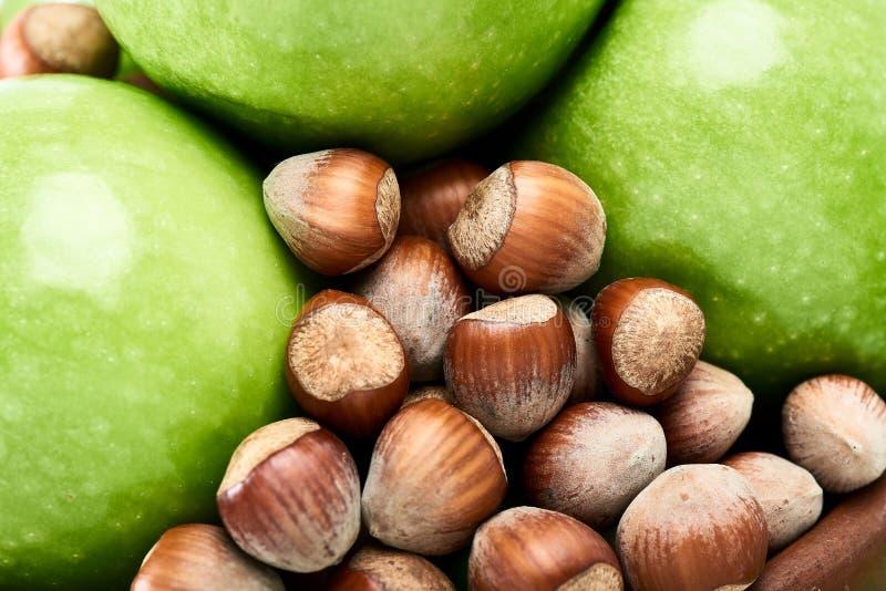 Καφετιά φουντούκια και δονούμενος πράσινος της φρέσκιας κινηματογράφησης σε πρώτο πλάνο μήλων Γιαγιάδων Σμίθ στοκ εικόνα