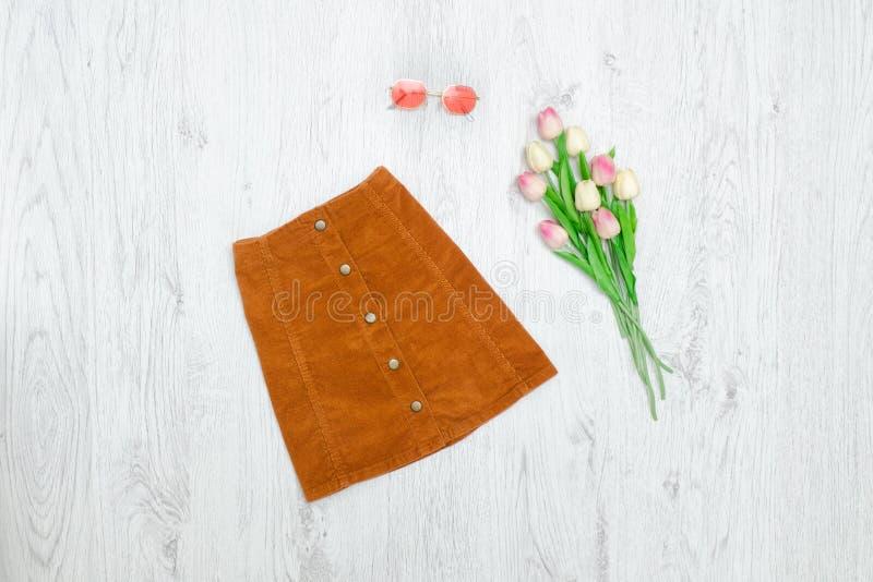 Καφετιά φούστα με τα κουμπιά, τα ρόδινες sunglaasses και την ανθοδέσμη των τουλιπών στοκ εικόνες με δικαίωμα ελεύθερης χρήσης