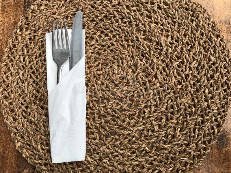 Καφετιά ψάθινη πετσέτα με τα μαχαιροπήρουνα στον ξύλινο πίνακα Εξυπηρέτηση, δίκρανο και μαχαίρι στοκ φωτογραφίες με δικαίωμα ελεύθερης χρήσης
