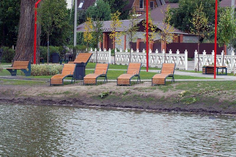 Καφετιές ξύλινες καρέκλες γεφυρών στην ακτή μιας λίμνης σε ένα πάρκο στοκ εικόνα