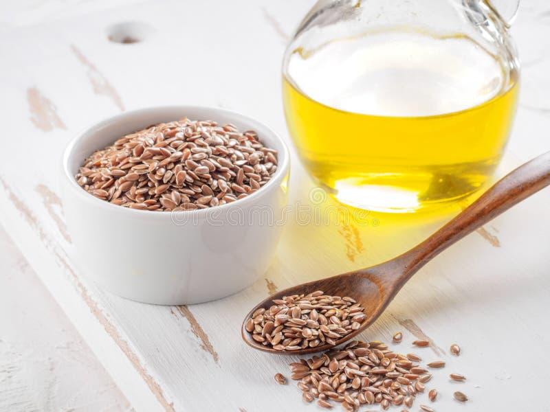 Καφετιοί σπόροι λιναριού και flaxseed στενός επάνω πετρελαίου στοκ φωτογραφία με δικαίωμα ελεύθερης χρήσης