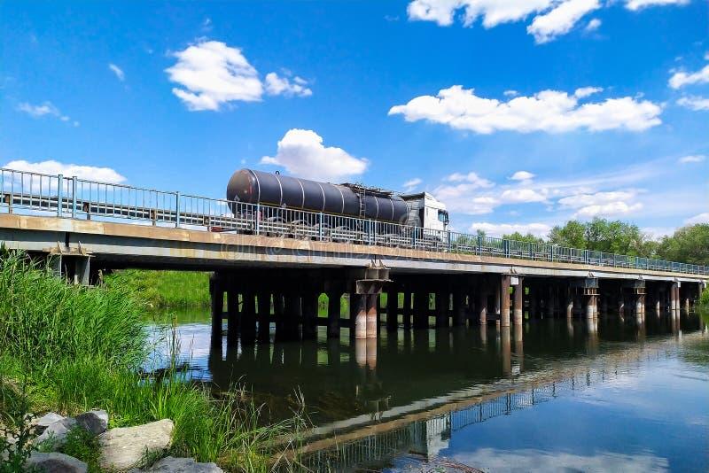Καύσιμα μεταφορών φορτηγών βυτιοφόρων βενζίνης ή αερίου σε ένα βενζινάδικο μέσω ενός ποταμού γεφυρώνουν μια ηλιόλουστη ημέρα στοκ εικόνες με δικαίωμα ελεύθερης χρήσης