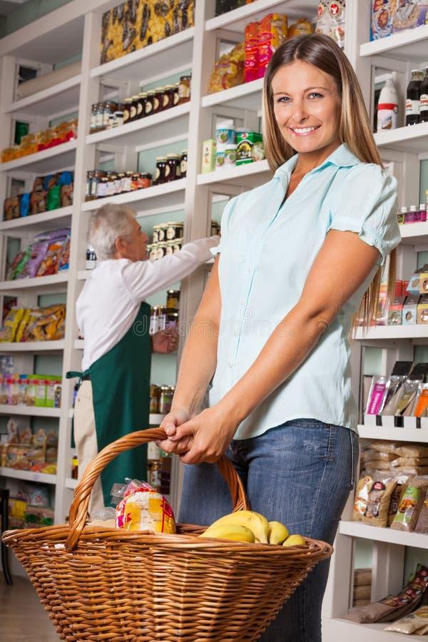 Καλάθι αγορών εκμετάλλευσης γυναικών με τον πωλητή μέσα στοκ εικόνες