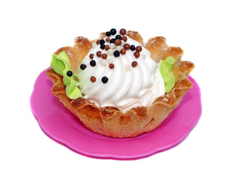 Καλάθι κέικ με την άσπρη κρέμα που διακοσμείται με τις μικρές σφαίρες στοκ εικόνα με δικαίωμα ελεύθερης χρήσης