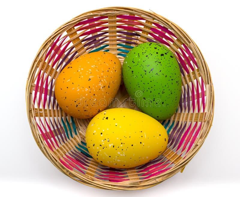 Καλάθι των ζωηρόχρωμων αυγών Πάσχας που απομονώνονται στοκ φωτογραφία