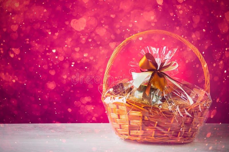 Καλάθι δώρων με τα εορταστικά μόρια, πορφυρό υπόβαθρο στοκ φωτογραφίες