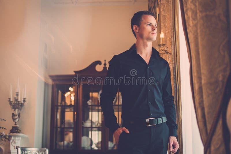 Καλά-ντυμένο άτομο στο εσωτερικό σπιτιών πολυτέλειας στοκ εικόνες με δικαίωμα ελεύθερης χρήσης