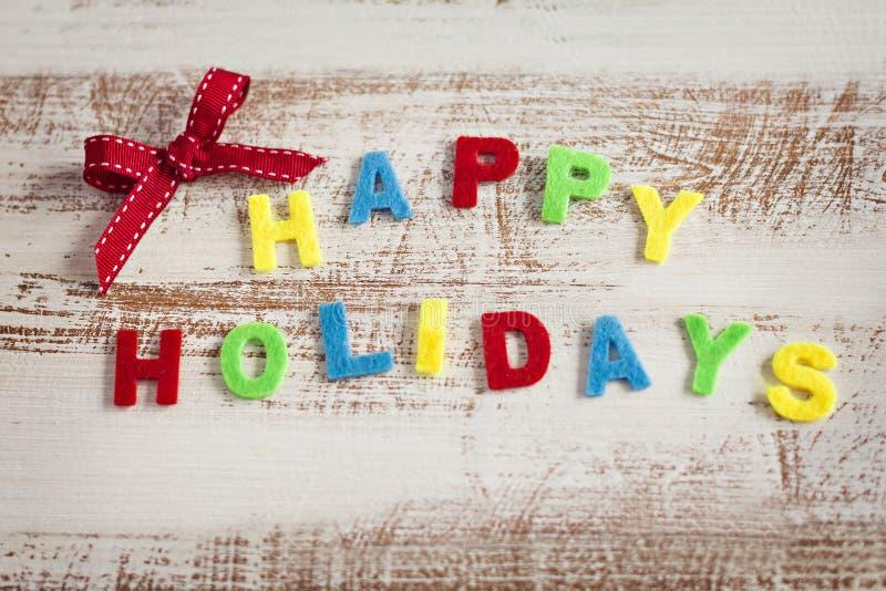 Καλές διακοπές giftcard καμένος με πολύχρωμες επιστολές στο ξύλινο υπόβαθρο στοκ εικόνες