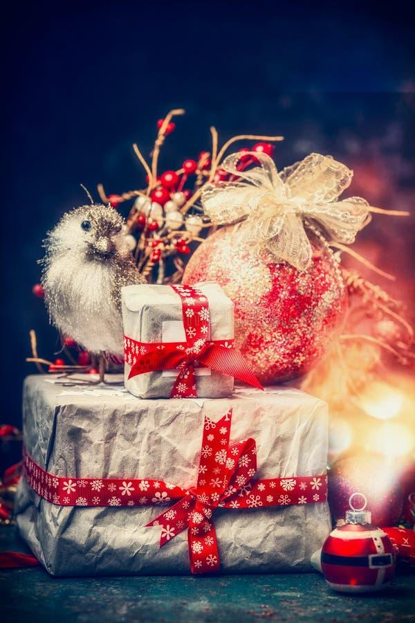 Καλή κάρτα Χριστουγέννων με τα υπέροχα συσκευασμένα δώρα, τις σφαίρες διακοπών, το πουλί και τον εορταστικό φωτισμό bokeh στοκ εικόνα με δικαίωμα ελεύθερης χρήσης
