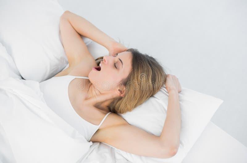 Καλή νέα γυναίκα που χασμουριέται στο κρεβάτι της στοκ εικόνες