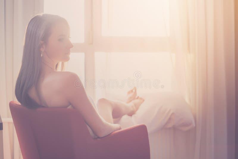 Καλή συνεδρίαση γυναικών και κοίταγμα μέσω μιας ανατολής ή ενός ηλιοβασιλέματος θαυμασμού παραθύρων στοκ φωτογραφία με δικαίωμα ελεύθερης χρήσης