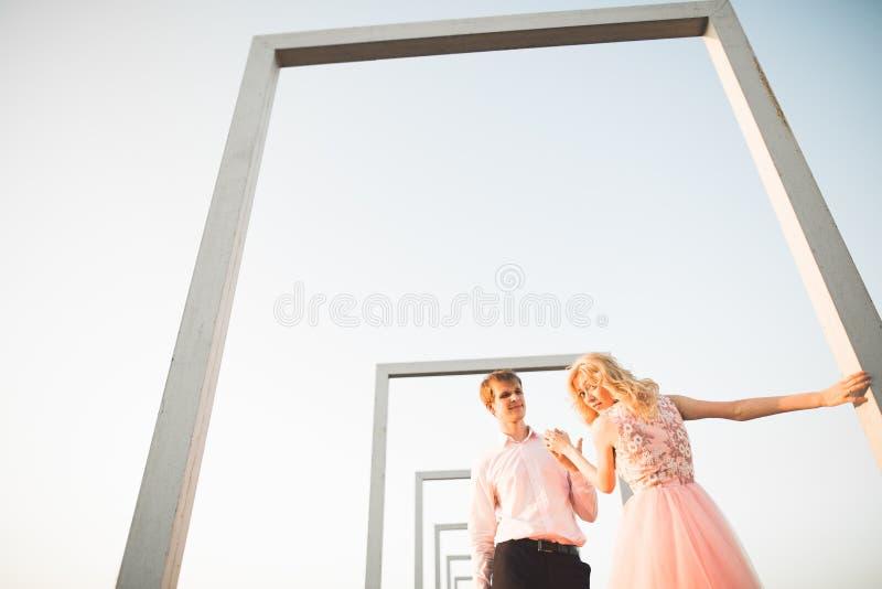 Καλή όμορφη τοποθέτηση ζευγών μόδας στη στέγη με το υπόβαθρο πόλεων Νεαρός άνδρας και αισθησιακός ξανθός υπαίθριος lifestyle στοκ φωτογραφία με δικαίωμα ελεύθερης χρήσης