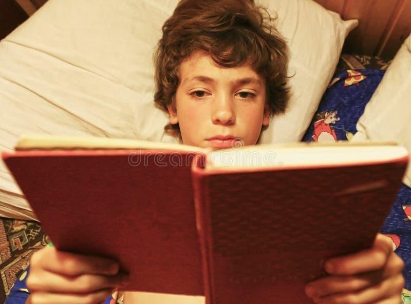Καλαμώνοντας βιβλίο αγοριών στη φωτογραφία κρεβατιών κοντά επάνω στοκ εικόνες