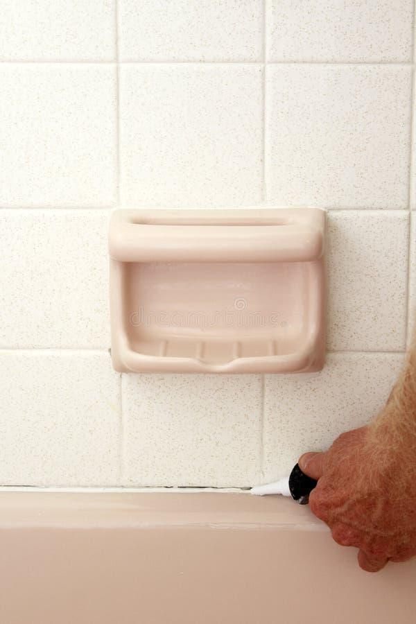 Καλαφάτισμα μεταξύ της μπανιέρας και του τοίχου στοκ εικόνα