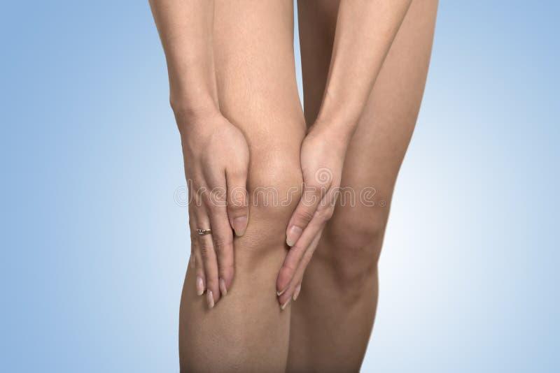 Καλλιεργημένα χέρια γυναικών εικόνας σχετικά με το επίπονο γόνατο ποδιών στοκ εικόνα με δικαίωμα ελεύθερης χρήσης