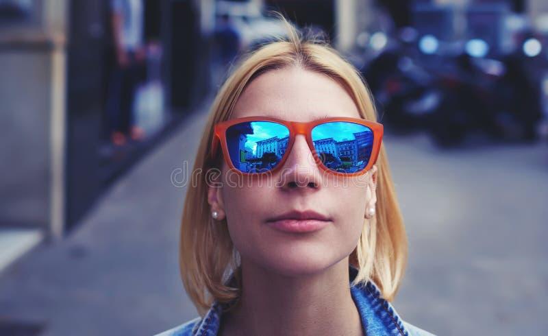 Καλλιεργημένη εικόνα με το χαριτωμένο κορίτσι hipster στα θερινά γυαλιά ηλίου που κοιτάζει στη κάμερα στοκ φωτογραφία