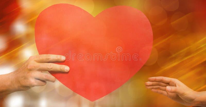 Καλλιεργημένη εικόνα του άνδρα που δίνει τη μορφή καρδιών στη γυναίκα ενάντια στο bokeh στοκ φωτογραφίες