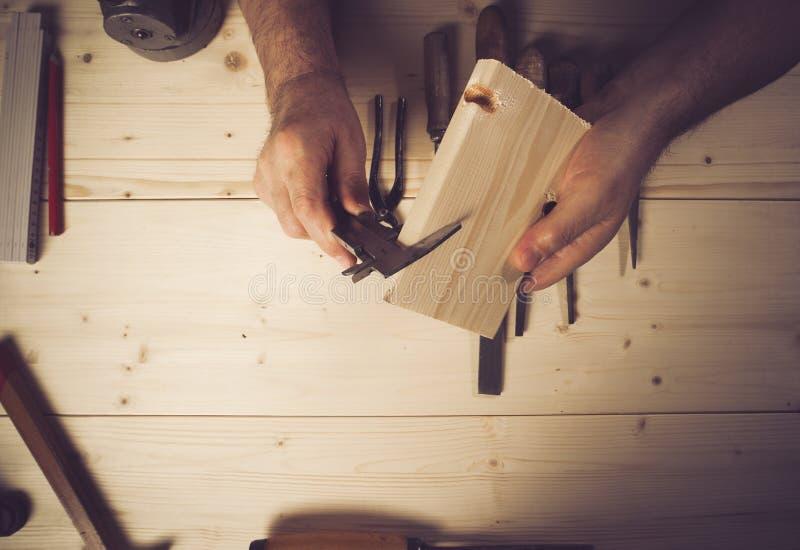 Καλλιεργημένη εικόνα του ανώτερου ξυλουργού που μετρά το ξύλο στο εργαστήριο στοκ φωτογραφία