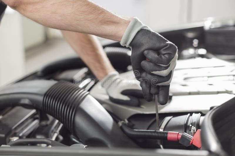 Καλλιεργημένη εικόνα του αυτοκινητικού μηχανικού αυτοκινήτου επισκευής στο αυτοκινητικό κατάστημα στοκ φωτογραφίες