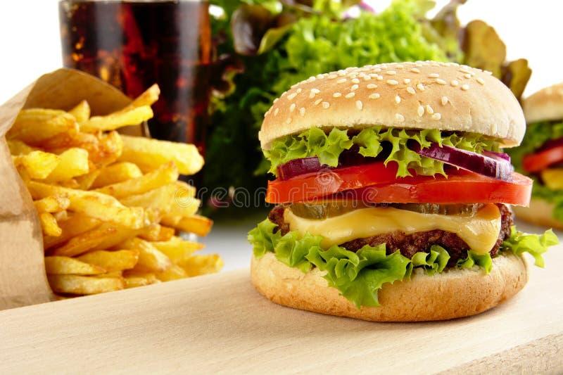 Καλλιεργημένη εικόνα cheeseburger, τηγανιτές πατάτες, ποτήρι της κόλας στο ξύλο στοκ εικόνα