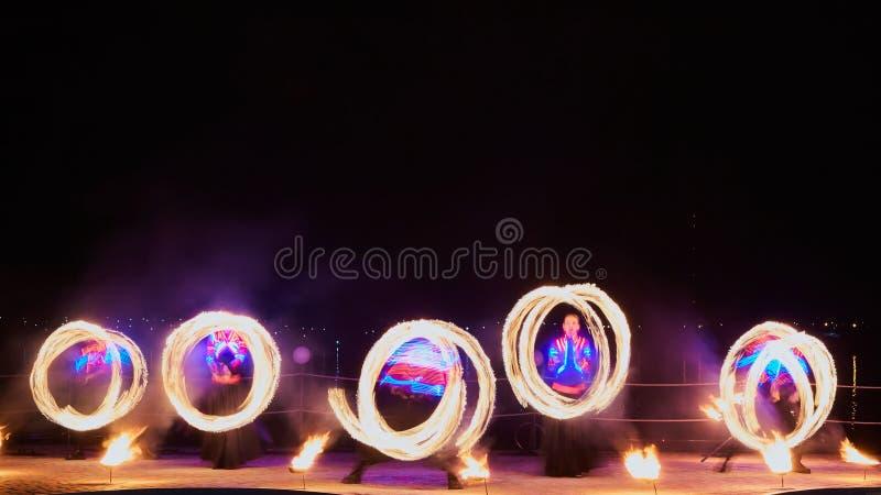Καλλιτέχνες που κάνουν ταχυδακτυλουργίες με το κάψιμο poi& x27 s στην απόδοση πυρκαγιάς στοκ εικόνες