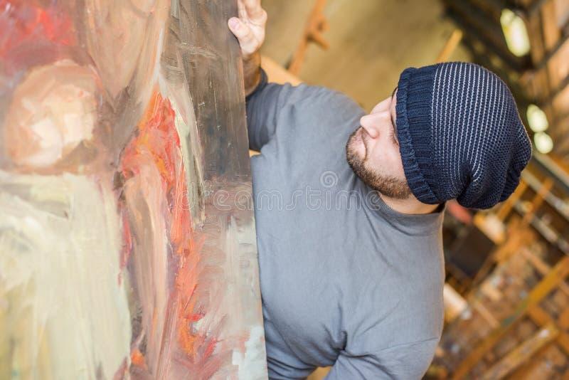 Καλλιτέχνης/δάσκαλος που κρατά το έργο τέχνης του στοκ φωτογραφίες