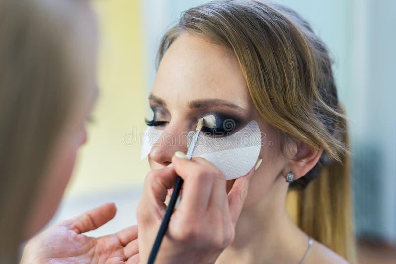 Καλλιτέχνης σύνθεσης που κάνει τα καπνώδη μάτια makeup στο όμορφο νέο κορίτσι στοκ εικόνες με δικαίωμα ελεύθερης χρήσης