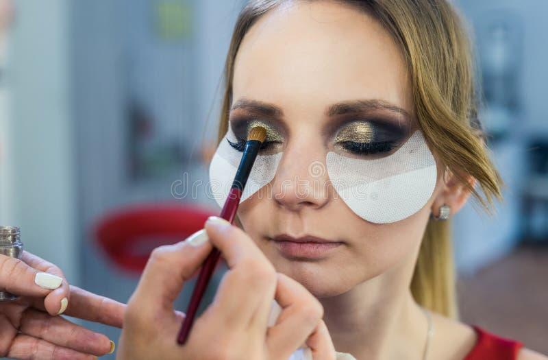 Καλλιτέχνης σύνθεσης που κάνει τα καπνώδη μάτια makeup στο όμορφο νέο κορίτσι στοκ εικόνα με δικαίωμα ελεύθερης χρήσης