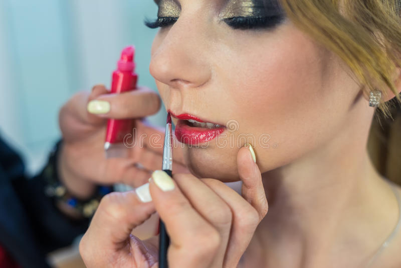 Καλλιτέχνης σύνθεσης που κάνει τα καπνώδη μάτια makeup στο όμορφο νέο κορίτσι στοκ φωτογραφία