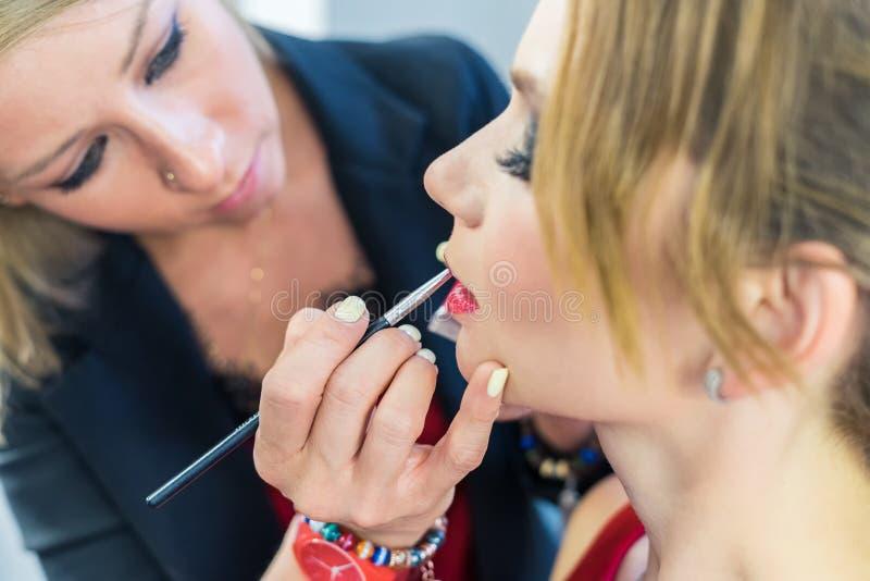 Καλλιτέχνης σύνθεσης που κάνει τα καπνώδη μάτια makeup στο όμορφο νέο κορίτσι στοκ φωτογραφία με δικαίωμα ελεύθερης χρήσης