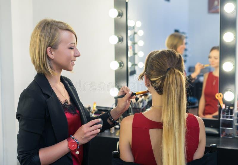 Καλλιτέχνης σύνθεσης που κάνει makeup στο όμορφο νέο κορίτσι στοκ φωτογραφία με δικαίωμα ελεύθερης χρήσης