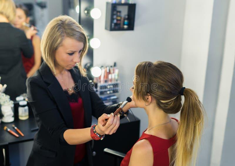 Καλλιτέχνης σύνθεσης που κάνει makeup στο όμορφο νέο κορίτσι στοκ φωτογραφίες