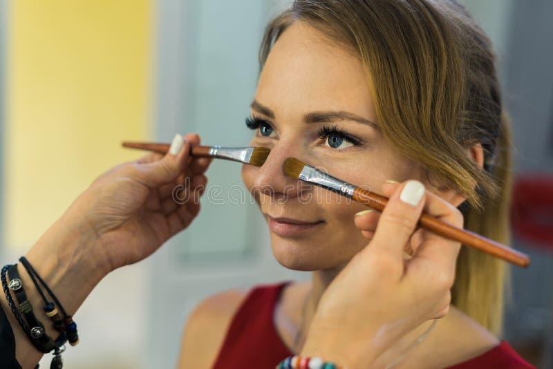 Καλλιτέχνης σύνθεσης που κάνει makeup στο όμορφο νέο κορίτσι στοκ εικόνες