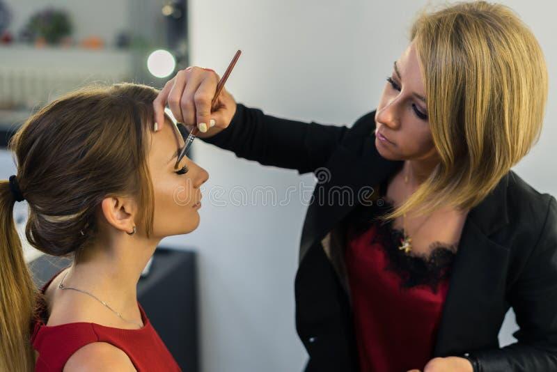 Καλλιτέχνης σύνθεσης που κάνει makeup στο όμορφο νέο κορίτσι στοκ φωτογραφία