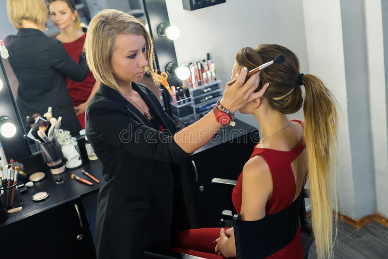 Καλλιτέχνης σύνθεσης που προετοιμάζεται για να κάνει makeup στο όμορφο νέο κορίτσι στοκ φωτογραφίες