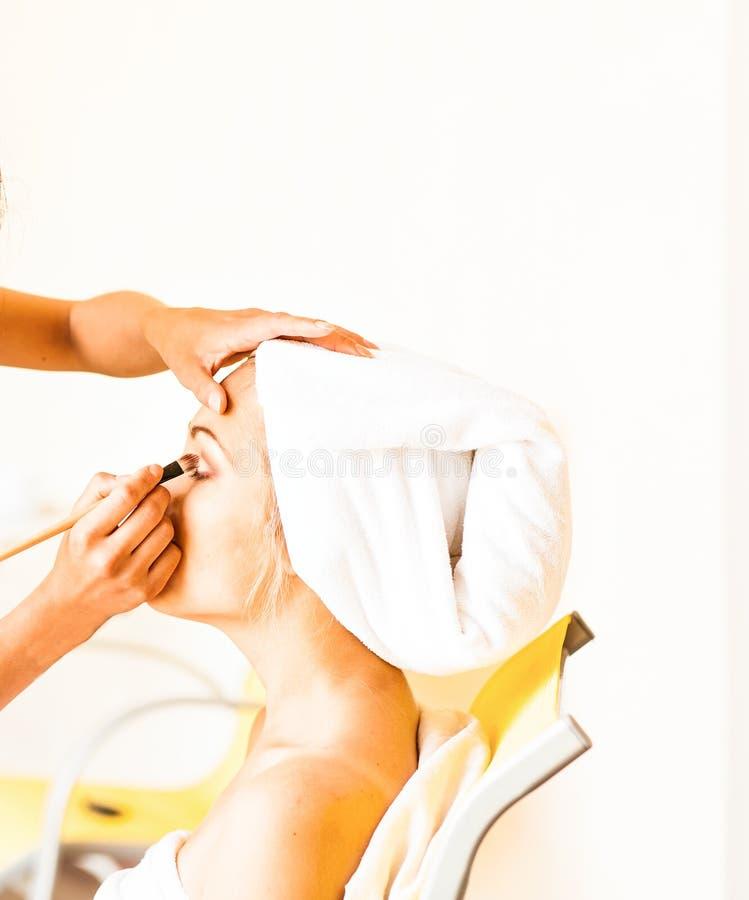 Καλλιτέχνης Makeup που προετοιμάζει τη νύφη πριν από το γάμο ένα πρωί στοκ εικόνες