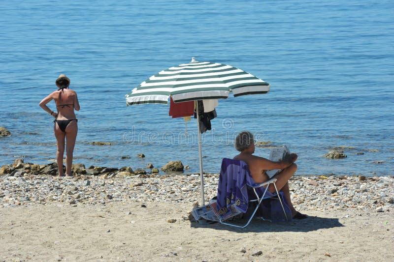 Καλοκαίρι ένα ζεύγος με την ομπρέλα παραλιών τους στην παραλία στοκ φωτογραφία με δικαίωμα ελεύθερης χρήσης