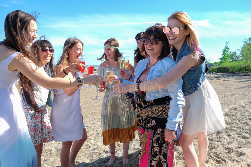 Καλοκαιρινές διακοπές και έννοια διακοπών - ομάδα νέων γυναικών με τα ποτά στην παραλία στοκ φωτογραφία