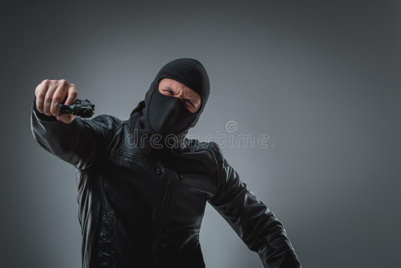 Καλυμμένος ληστής με το πυροβόλο όπλο, που εξετάζει τη κάμερα στοκ φωτογραφία