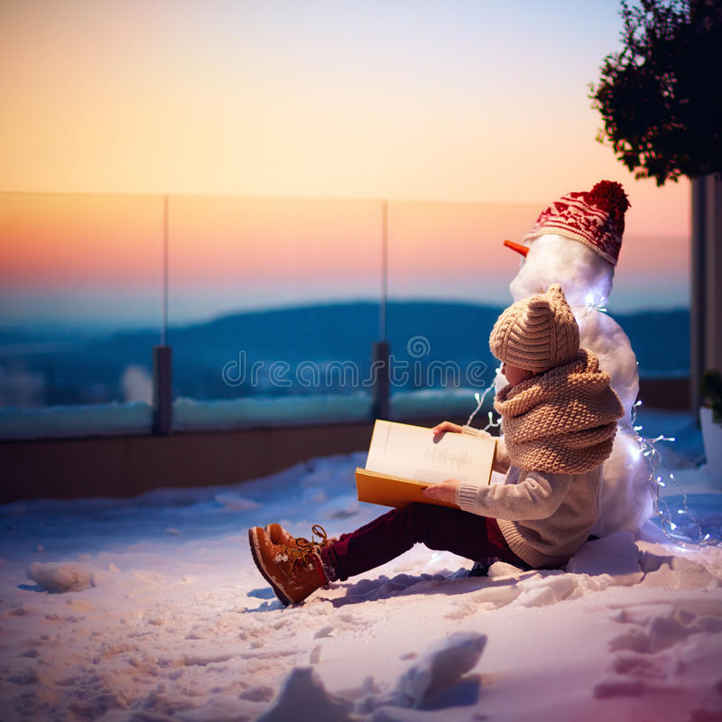 καλυμμένος χειμώνας ιστορίας χιονιού σπιτιών νεράιδων δασικός ξύλινος νέο αγόρι, παιδί που διαβάζει το ενδιαφέρον βιβλίο στο χιον στοκ φωτογραφία με δικαίωμα ελεύθερης χρήσης