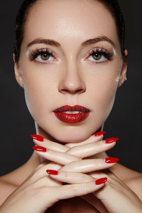 Καλλυντικά, μανικιούρ στα καρφιά με τη φωτεινή κόκκινη στιλβωτική ουσία Σκούρο κόκκινο χειλική σύνθεση και χρώμα καρφιών στοκ εικόνες