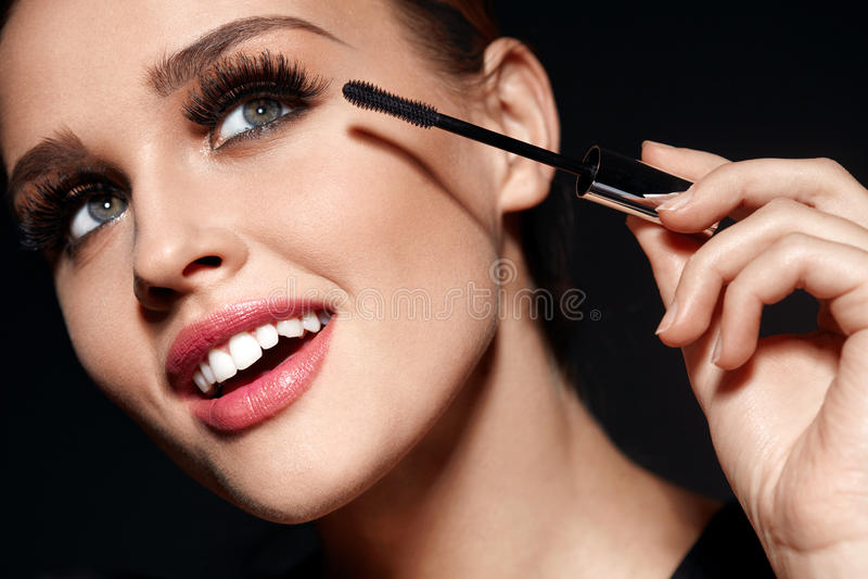 Καλλυντικά Όμορφη γυναίκα με τέλειο Makeup που εφαρμόζει Mascara στοκ φωτογραφίες
