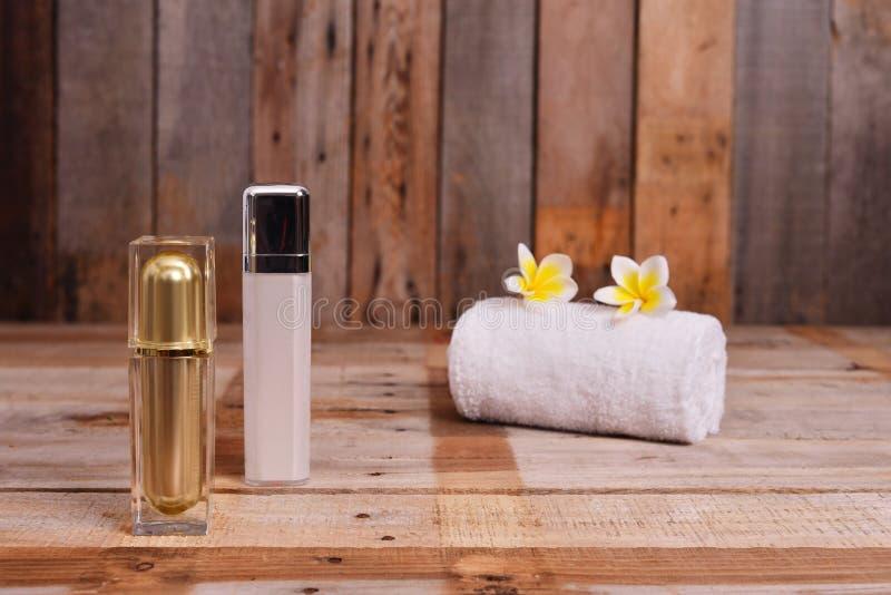 Καλλυντικό μπουκάλι και άσπρη πετσέτα με τα λουλούδια Frangipani στοκ εικόνα