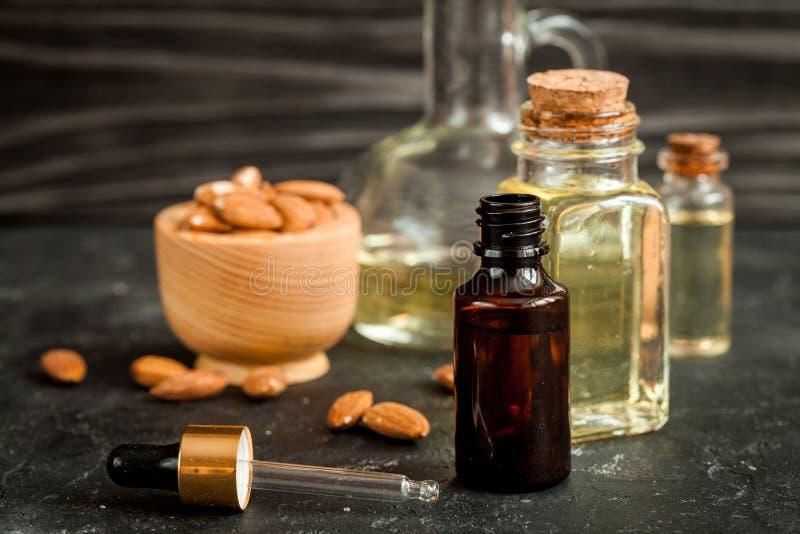 Καλλυντικό πετρέλαιο αμυγδάλων στο μπουκάλι γυαλιού στο σκοτεινό ξύλινο υπόβαθρο στοκ φωτογραφίες με δικαίωμα ελεύθερης χρήσης